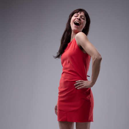 Glückliche Frau im roten Kleid stehend singend mit ihrer Hand zu ihrer Hüfte und einer Geste im Divastil über Grau mit Kopierraum