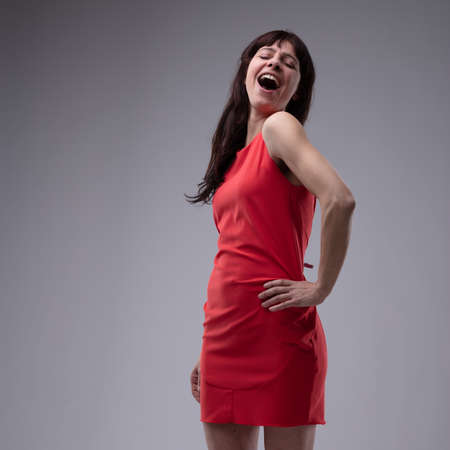 Happy woman in red dress standing singing with her hand to her hip and a diva style gesture over grey with copy space