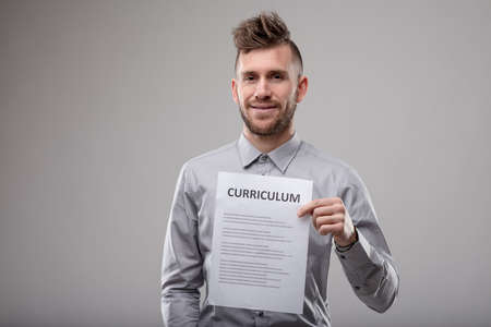 Trendy modern bearded young man holding up a typed Curriculum in front of his chest as he smiles at the camera over grey