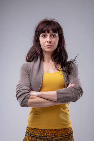 Sceptical woman staring at the camera with wide eyes and folded arms in a frontal portrait isolated on grey Imagens