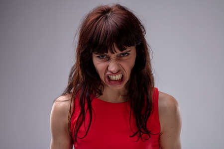 Angry temperamental woman snarling as she glowers at the camera with a fierce expression closeup over grey