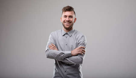 Happy confident slender bearded man with folded arms laughing at the camera isolated on grey