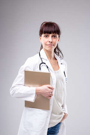 Busy female doctor pausing to look at the camera with a patients medical records under her arm and a quiet smile over a grey studio background