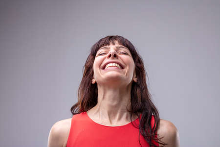 Elated relaxed woman with a wide warm beaming smile tilting her head back with closed eyes isolated on grey