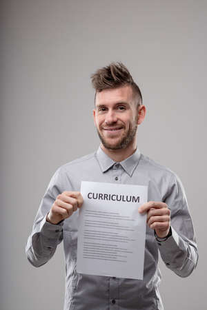 Smiling happy confident man applying for a job holding up a typed copy of a curriculum vitae as he grins at the camera over grey Imagens