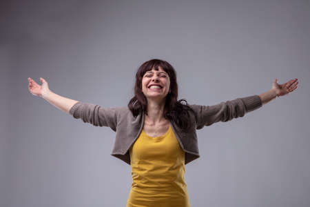 Happy elated woman celebrating with outspread arms and a beaming smile of delight and pleasure over grey