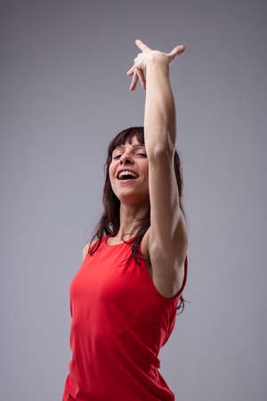 Attractive woman dancing and singing with her arm raised gracefully above her head isolated on grey