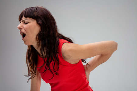 Woman with backache groaning in pain as she holds her hand to her lower back in a close up side view on grey Imagens