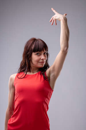 Woman diva gesturing gracefully with her hand with a superior smile as she looks down at the camera, low angle over grey