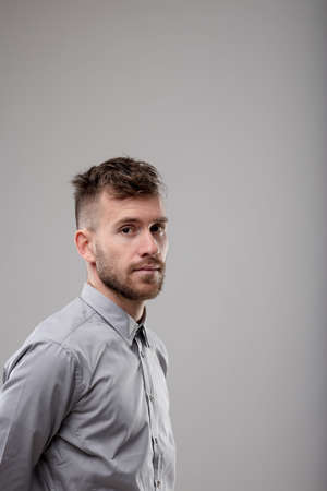 Serious bearded man with a modern haircut standing looking sideways at camera with a thoughtful expression Imagens