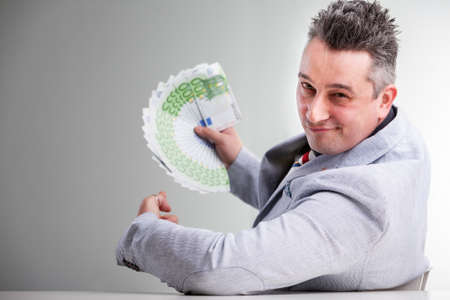 Smiling businessman holding a handful of 100 euro banknotes leaning on the table with a beaming smile as he celebrates his business success or winning a fortune Imagens