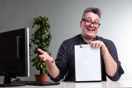 Laughing gleeful businessman gesturing and holding up a blank clipboard with copy space as he celebrates his success seated at a desk with a desktop computer Banco de Imagens