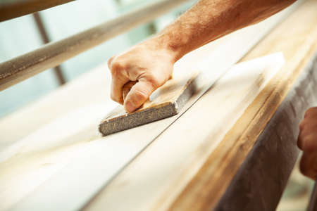 Angled view of man using wood sander with handle to smooth out wood plank sitting on top of table