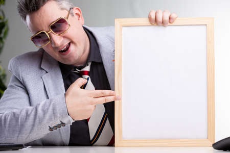 Smart successful man wearing a suit and dark glasses pointing to a blank notice or white card in a plain wooden picture frame with a smile