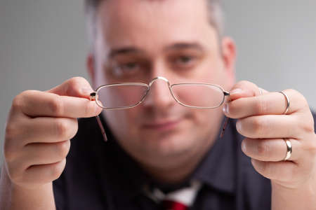 Businessman holding a pair of eyeglasses with metal frames in his hands with a thoughtful expression, selective focus to the spectacles
