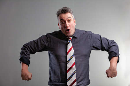 Man fooling around having fun imitating an ape with open mouth and furled back hands over a grey studio background