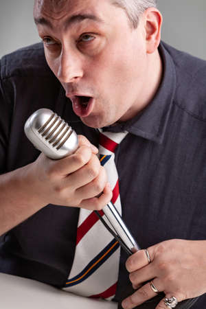 Man engrossed in his music holding a microphone as he sings a lyric or song with a faraway expression in a close up cropped portrait
