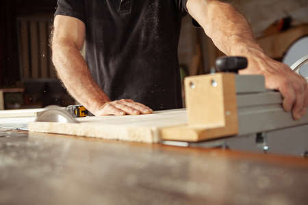 Carpenter working with a bench saw cutting planks of wood in a workshop in a close up low angle view of his hands Imagens