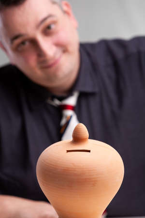 Smiling successful businessman with a stylish pottery money box or piggy bank in the foreground in a conceptual image