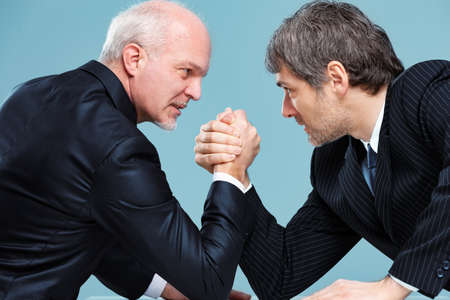Two businessmen challenging each other for a leadership position trying to dominate by arm wrestling and staring into each others eyes Imagens