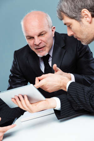 Two businessmen working as a team collaborating and sharing ideas during a meeting referring to a handheld tablet during their discussion Imagens