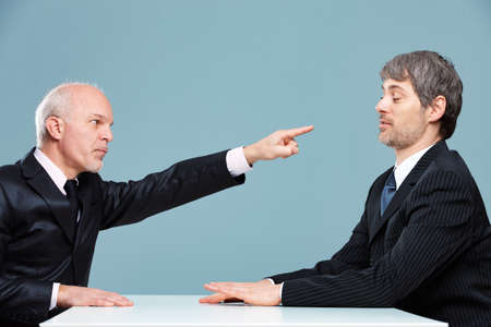 Two businessmen having an argument in the office with the more dominant partner pointing a finger of accusation as the other tries to pacify him with a hand gesture