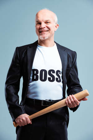Gleeful Boss wearing a T-shirt with text standing in his suit wielding a baseball bat with a beaming smile in a humorous spoof isolated on blue grey