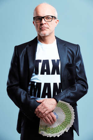 Tax Man wearing a T-shirt with text standing holding a handful of 100 euro notes staring at the camera with a serious deadpan expression over blue in a conceptual image Imagens
