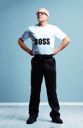 Supercilious haughty Boss stereotype with a studio shot of a senior man wearing a Boss T-shirt standing with hands on hips look up and off to the side Imagens