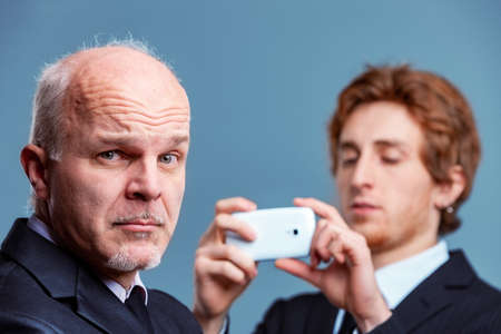 Charismatic conservative senior businessman pulling a wry quizzical face at the camera as a younger colleague or partner prepares to photograph him on his mobile phone