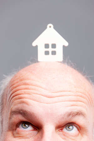 Senior balding man looking up at a model house balanced on the top of his head in a close up on his eyes in a conceptual image of home ownership, debt, realty and aspirations
