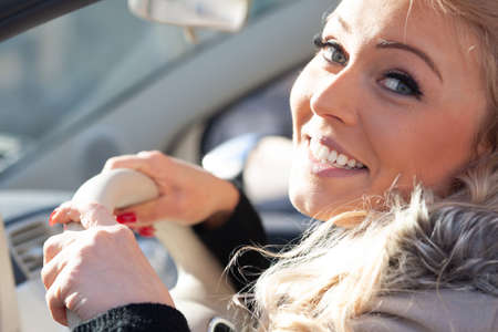 friendly young blond woman driving a car looking back though the side window with a smile as she clings to her steering wheel