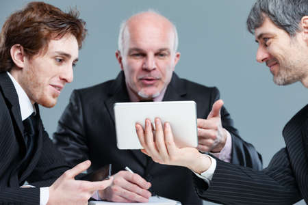 Two smiling employees in a discussion with a senior holding up a tablet during a meeting gesturing at a breakthrough idea or solution