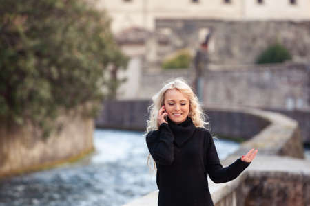 Pretty slender young blond woman talking on her mobile with a smile as she walks through a historic town with stone walls
