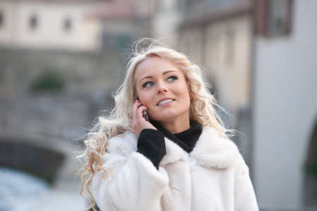 Stylish young blond woman in a white winter coat walking through town using a mobile listening to the conversation with a thoughtful smile