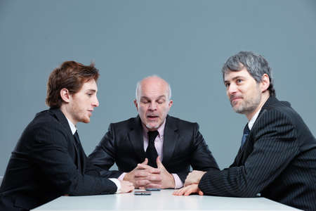 Senior businessman boring his colleagues with his long-winded discussion as they sit around an office table Imagens