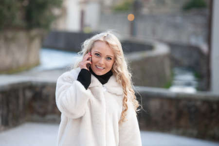 Attractive blond woman in a stylish winter coat walking through town over a canal chatting on her mobile and smiling