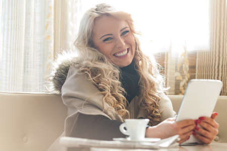 Charming beautiful young bland woman seated in a restaurant drinking coffee holding a tablet looking at the camera with a vivacious smile