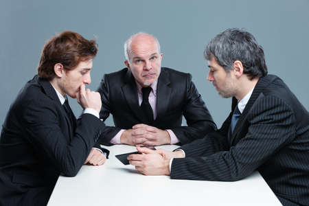 Three businessmen having a serious discussion during a meeting seated around an office table with the older man looking thoughtfully up at the camera Imagens