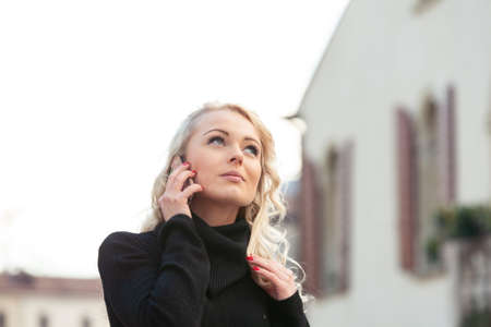 Young attractive blond woman listening intently to a call on her mobile phone looking up with a pensive expression outdoors in town Imagens