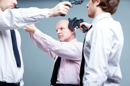 Business stand-off or stalemate concept with three businessman standing in a circle pointing guns at each others heads each determined not to give way