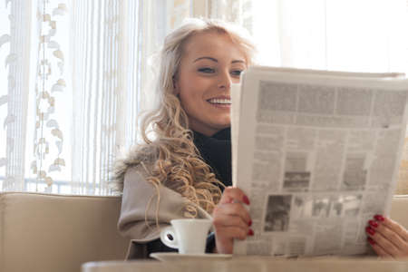 Pretty young blond woman reading the morning newspaper as she relaxes in a cafe enjoying a cup of espresso coffee Imagens