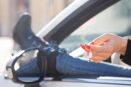 Woman with her foot out of the car window smoking a cigarette with focus to her hand with manicured red nails