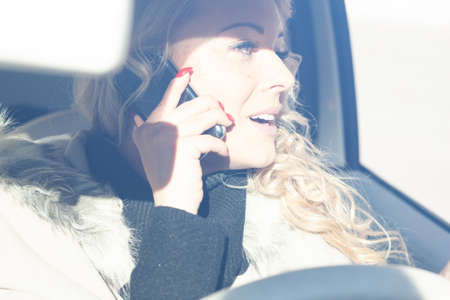 Young woman driver chatting on her mobile and looking out of the side window distracted by the conversation in a high key portrait