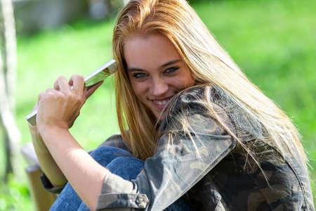 Divertente timida giovane donna che sorride alla telecamera da dietro la sua spalla mentre tiene un tablet nelle sue mani all'aperto in un parco