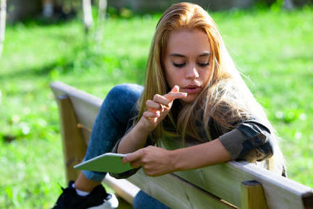 Young woman relaxing outdoors on a park bench with her leg draped over the top holding a tablet watching something on her long hair with finger poised Reklamní fotografie