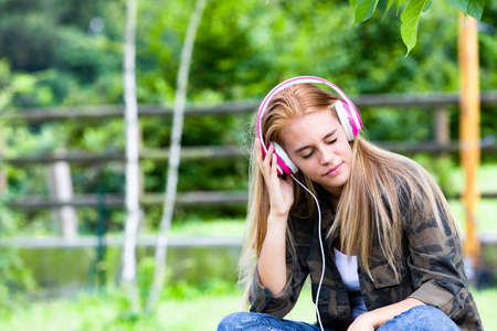 Young woman in countryside sat listening to music on headphones.