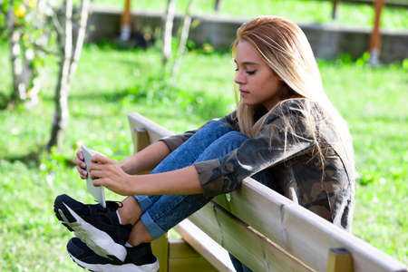 Trendy young woman in jeans and sneakers relaxing on a wooden bench in a lush green garden or park with her feet up over the back using a tablet -pc