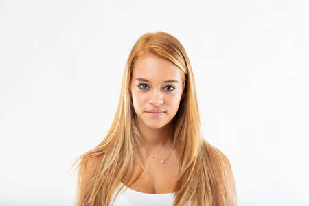 Portrait of an attractive young blond student with age related adolescent acne looking at the camera with a quiet smile isolated on white Reklamní fotografie