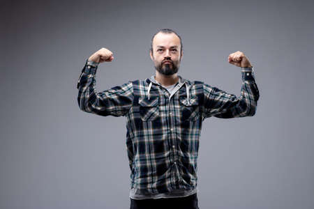 Macho bearded man in casual long sleeved shirt standing flexing his arms with a wry expression in an attempt to show off his biceps isolated on grey with copy space Reklamní fotografie